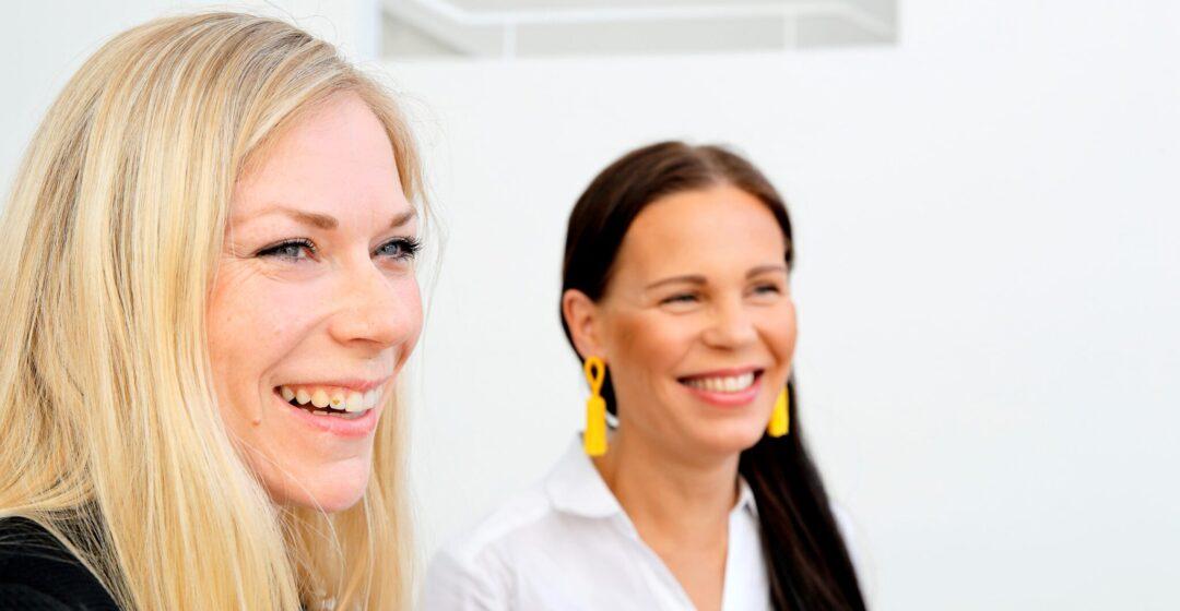 Vaalea ja tumma nainen hymyilevät