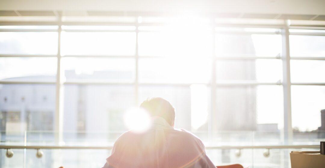 Mies lukee kirjaa auringonvalossa.