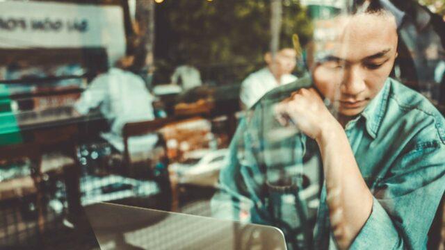 Mies istuu kahvilassa läppärin kanssa ja katsoo ulos.
