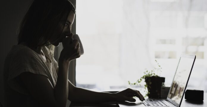 Woman drinking coffee and looking at her laptop.